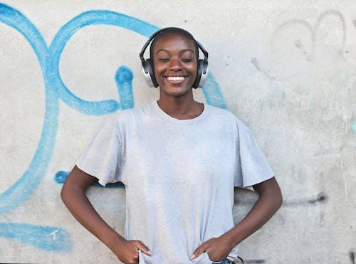 Woman in White Crew Neck T-shirt Wearing Black Headphones