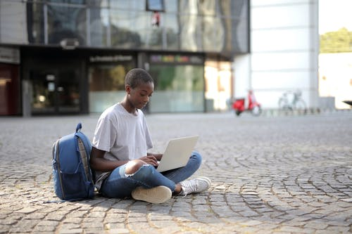 Man in White Crew Neck T-shirt Sitting on Brown Concrete Floor