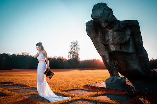 Woman in White Dress Standing Beside Man Statue