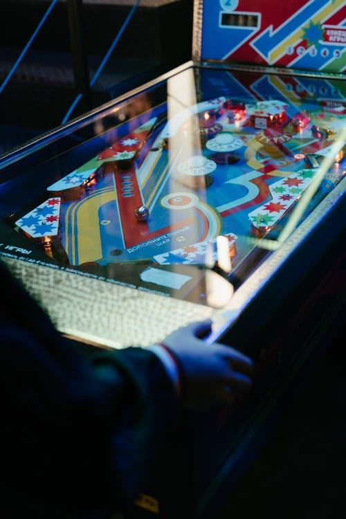 Person in Black Jacket Playing Arcade Game