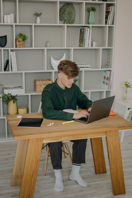 A Male Student in Green Long Sleeves Using a Laptop on a Wooden Desk