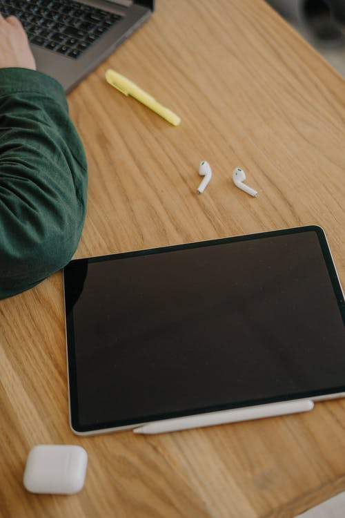 Close-Up Shot of an Ipad beside a Pair of Airpods on a Wooden Desk