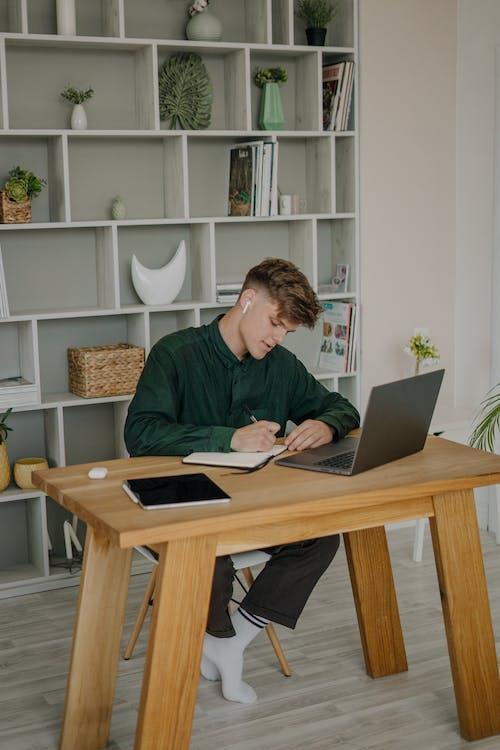 Man in Black Long Sleeve Shirt Sitting on Chair Using Macbook