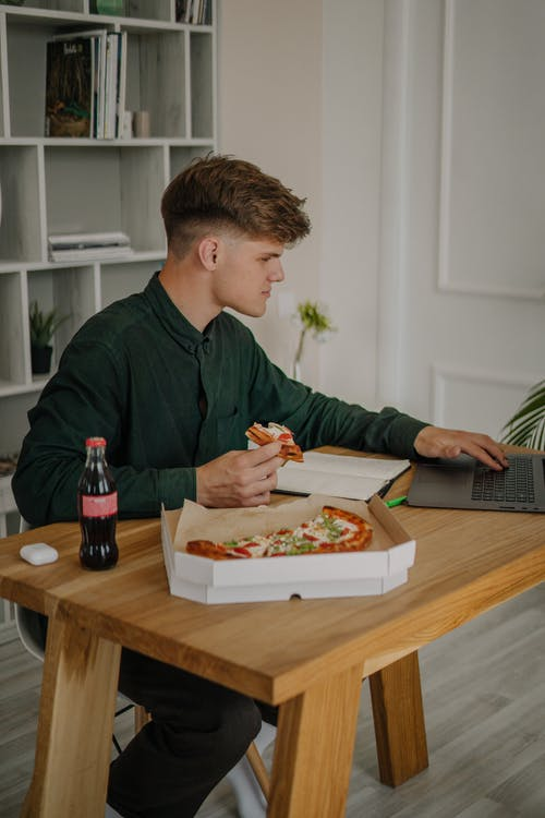 Man Eating Pizza and Working From Home