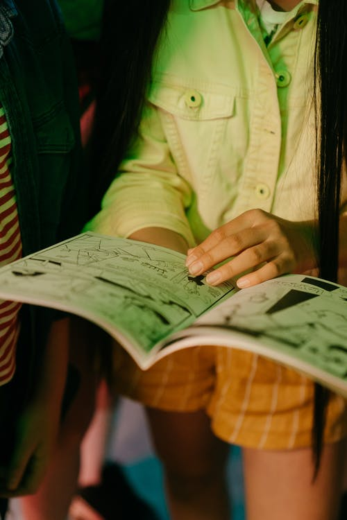 Woman in Green Button Up Shirt Holding Newspaper