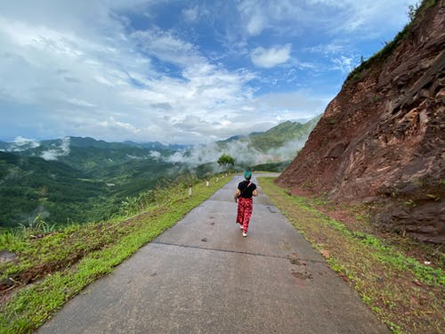 Full body back view of anonymous female traveler strolling on road along mountain and admiring green hills covered with fog