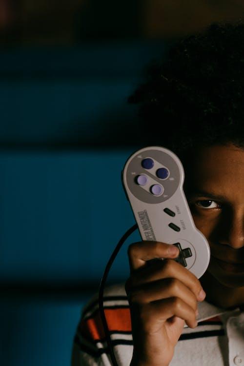 Crop black man showing retro gamepad in darkness