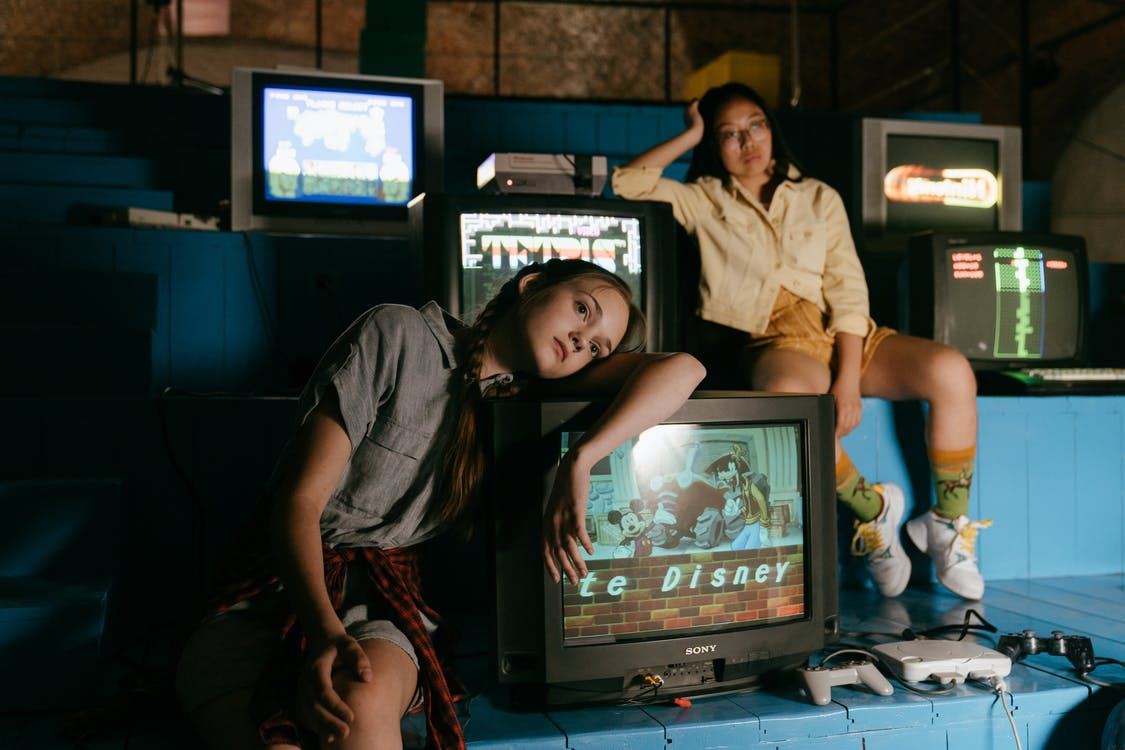 Woman in White Button Up Shirt Standing Beside Black Crt Tv