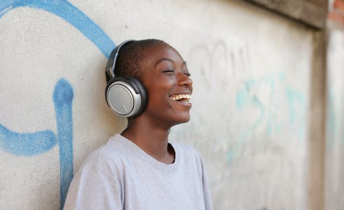 Smiling Boy in Gray Crew Neck Shirt Wearing Black and Silver Headphones