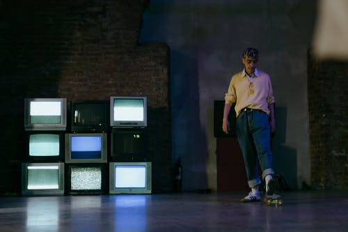 Man in Yellow Polo Shirt and Blue Denim Jeans Standing Near Black Flat Screen Computer Monitors