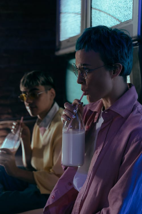 Man in Pink Dress Shirt Drinking from Clear Drinking Glass