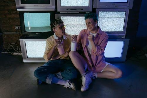 2 Women Sitting on Blue Chair