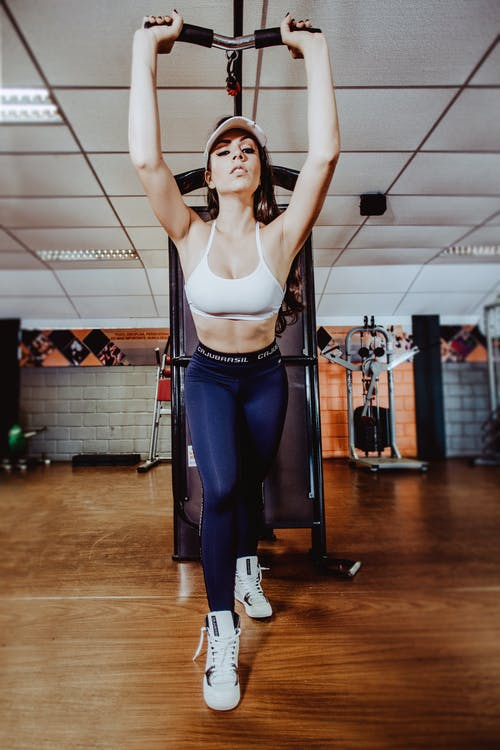 Sporty woman exercising on arm machine in gym