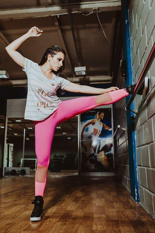 Flexible sportswoman stretching leg near wall in gym