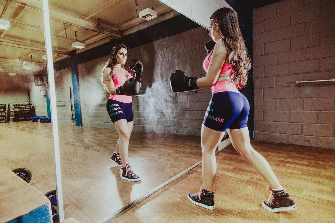 Back view concentrated sportswoman with perfect body wearing sportswear and boxing gloves punching air while looking in big wall mirror in modern gym