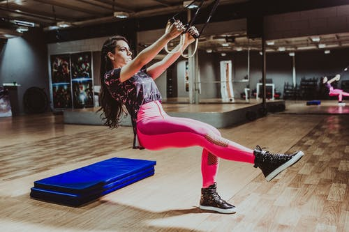 Determined sportswoman squatting with suspension straps in modern gym