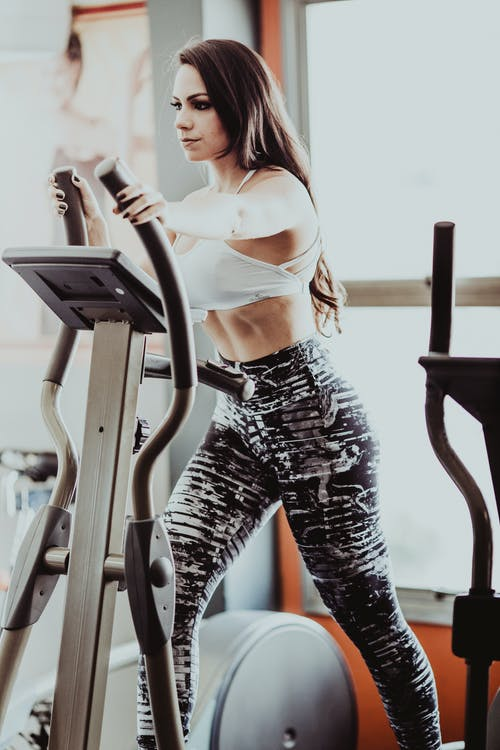 Sporty woman exercising on elliptical trainer machine