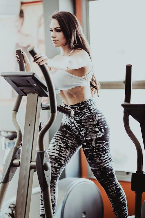 Determined fit sportswoman exercising on modern elliptical cross trainer in light fitness center