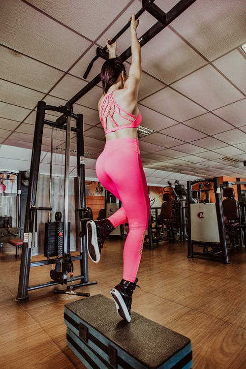 Back view anonymous fit sportswoman performing pull ups on bar in light spacious fitness club