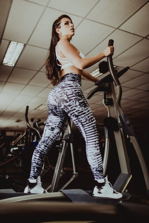Attractive sportswoman exercising on elliptical trainer
