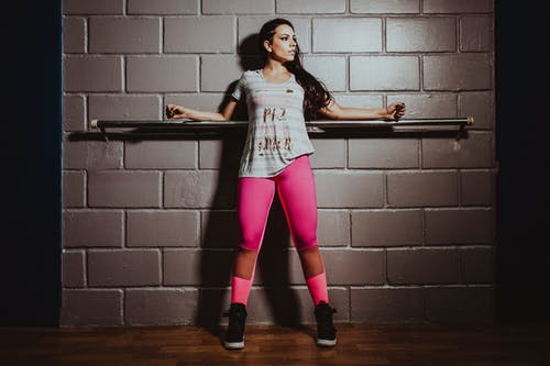Full body confident fit sportswoman wearing pink leggings standing with arms outstretched near metal bar in gym and looking away