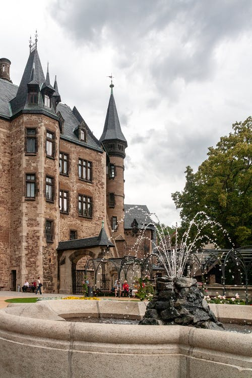 Low angle of fountain near ancient stone Wernigerode Castle with sharp spikes located in Germany on cloudy day