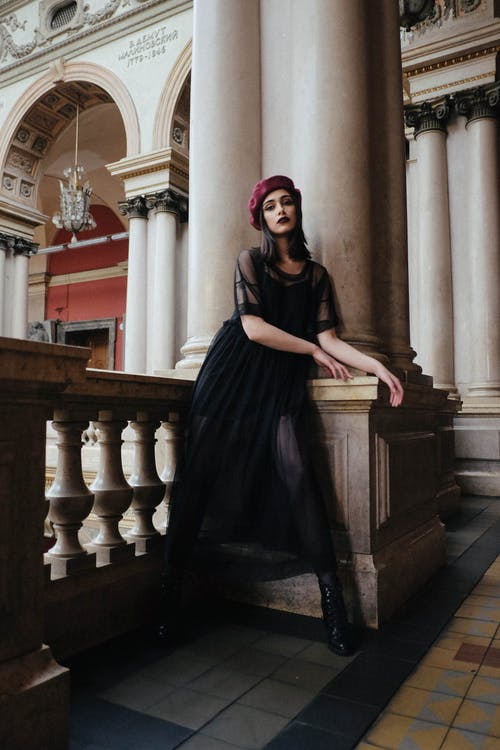 Young stylish woman in black apparel and beret standing near ornamental fence and column in old Applied Art Museum while looking at camera