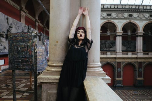Sensual stylish tattooed model leaned on columns in old museum