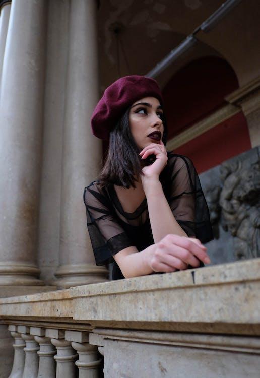 Feminine dreamy model in trendy outfit near stone fence