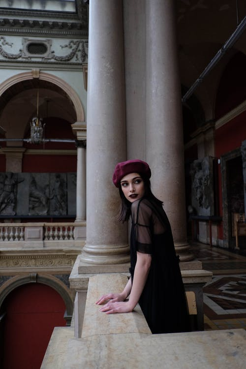 Side view of young dreamy female in stylish wear with beret looking away near columns in Applied Art Museum