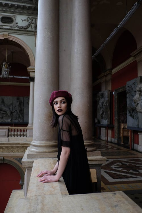 Side view of young wistful female in black clothes and beret looking away near masonry columns in Applied Art Museum in Russia