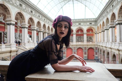 Stylish model with makeup in aged building with colonnade