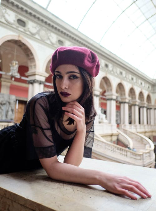Stylish model with makeup near stone fence in aged building