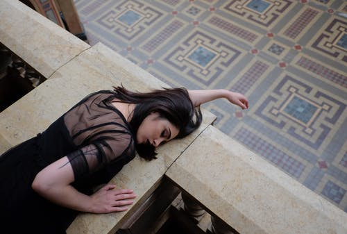 Stylish model in black wear lying on stone fence