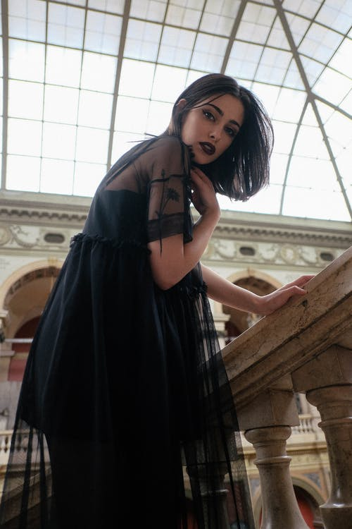 Elegant woman with makeup touching neck in old stone building