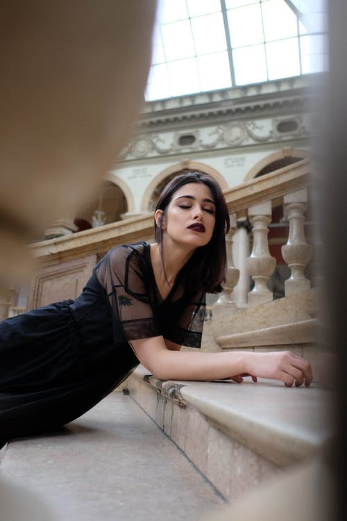 Charming dreamy woman with makeup in trendy apparel on staircase