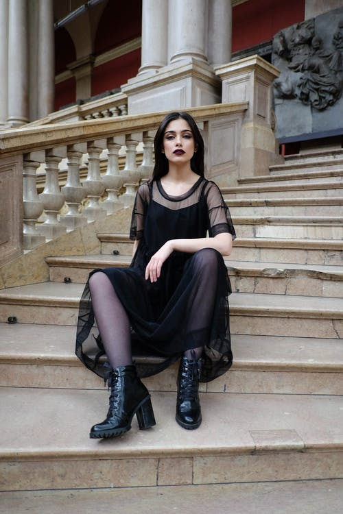 Fashionable woman in elegant apparel resting on stairs in building