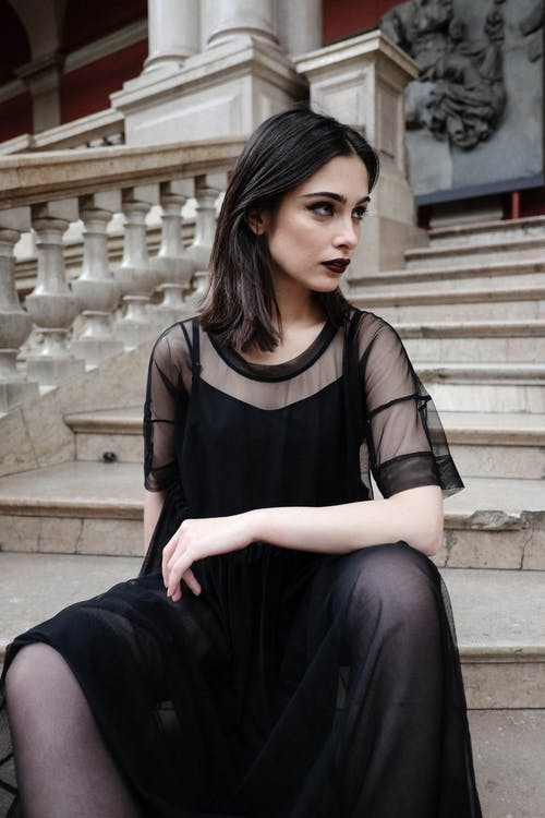 Stylish model in black outfit resting on stone stairs