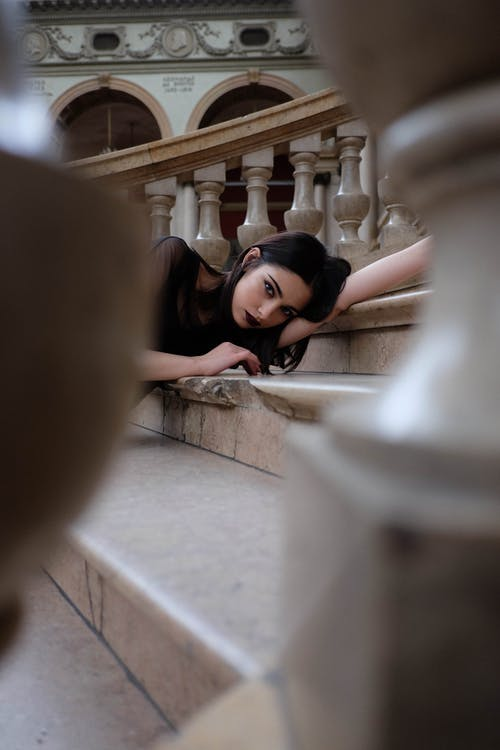Calm woman with dark makeup lying on stone stairs