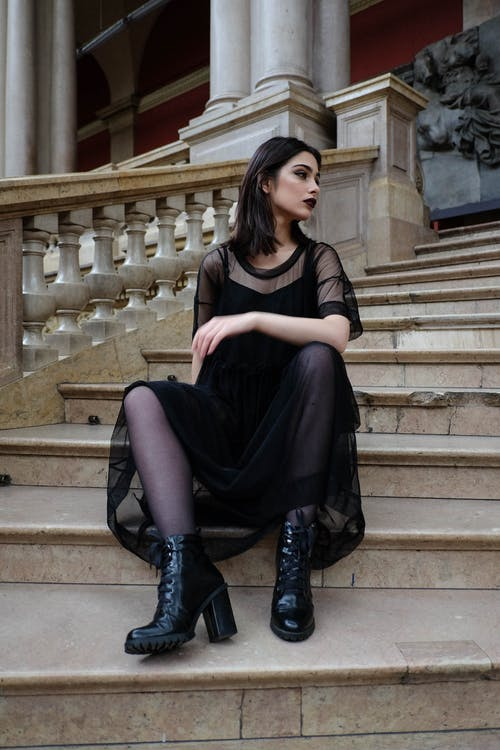 Woman in black dress and dark makeup sitting on stairs