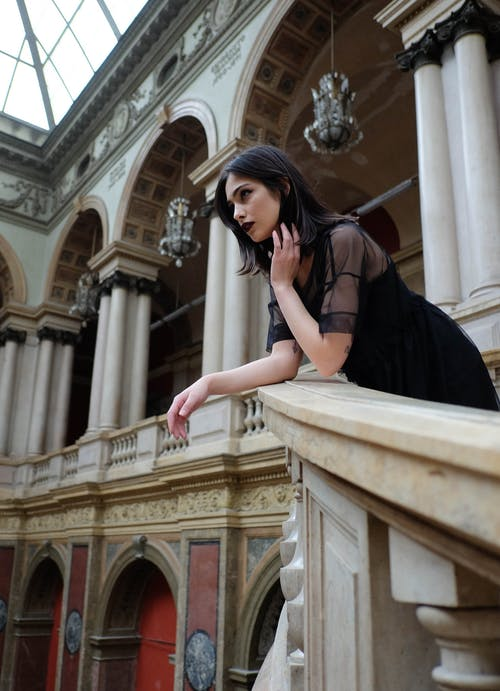 Calm woman in black lipstick leaning on stairs railing