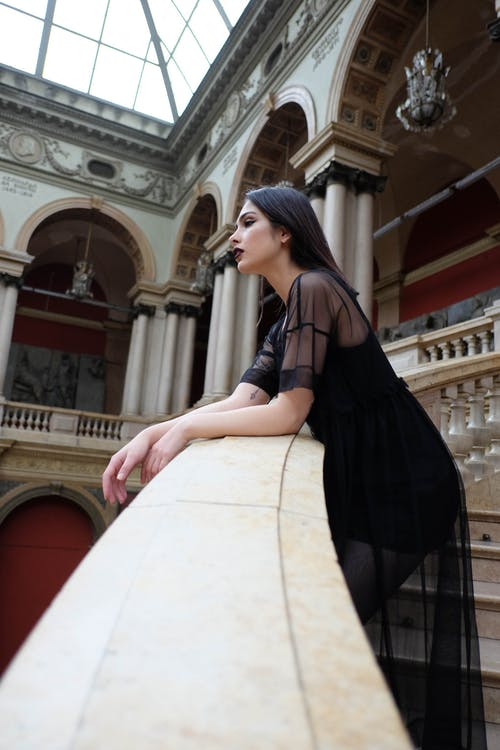 Woman in black elegant dress standing on stairs in palace