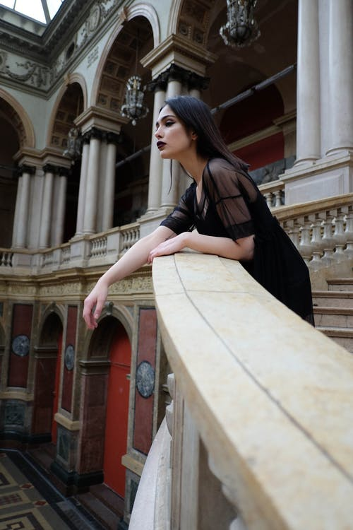 Woman with dark makeup leaning on railing in heritage building