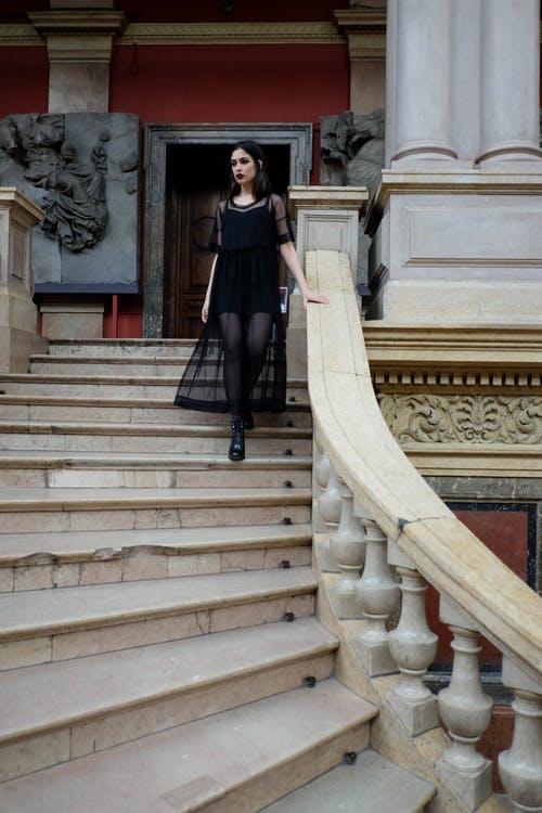 Emotionless woman in Gothic outfit walking downstairs in palace