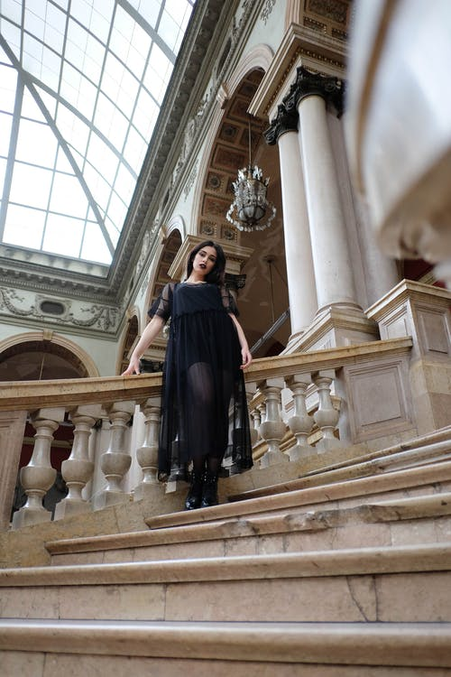 Gothic woman in black dress standing in heritage building
