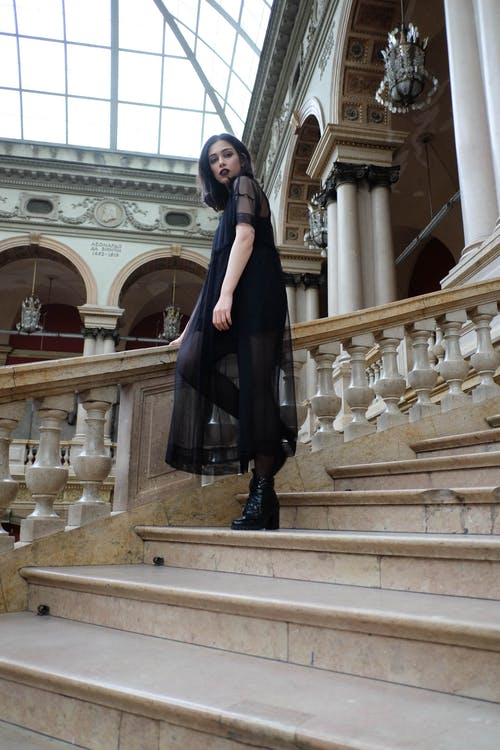 Fashionable woman in black maxi dress standing in historic building