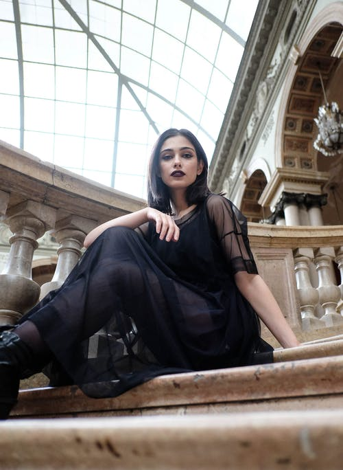 Attractive woman in black dress sitting on marble stairs