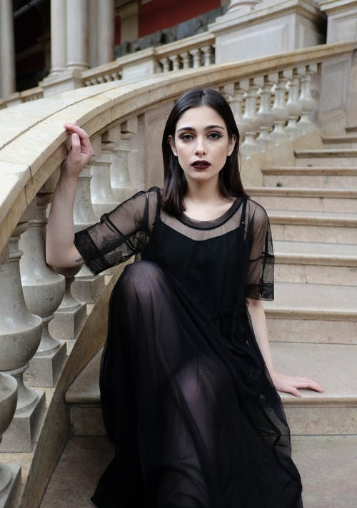 Gothic woman in black outfit sitting on stairs