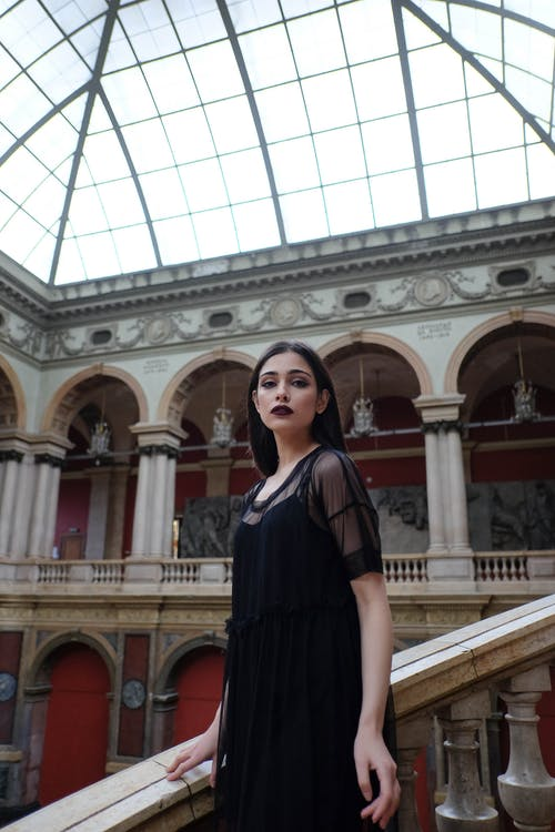 Wistful woman in black dress standing in historic palace