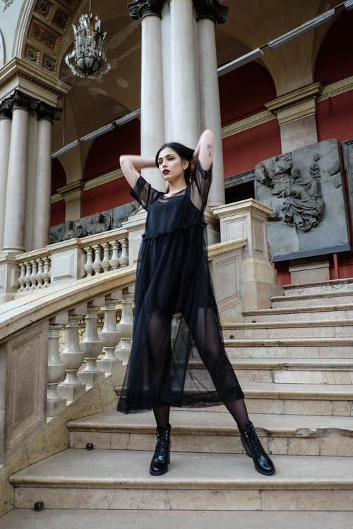 Graceful woman in black dress standing on palace steps
